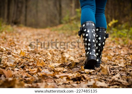 Girl walking through the forest with rain boots on - stock photo