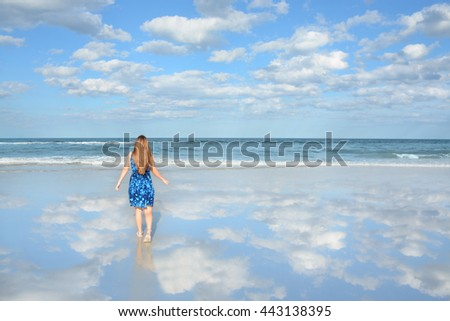 Girl walking toward water enjoying warm summer day on her vacation. Blue sky and ocean in the background. Beautiful clouds and sky reflected on the beach. Jacksonville, Florida, USA. - stock photo