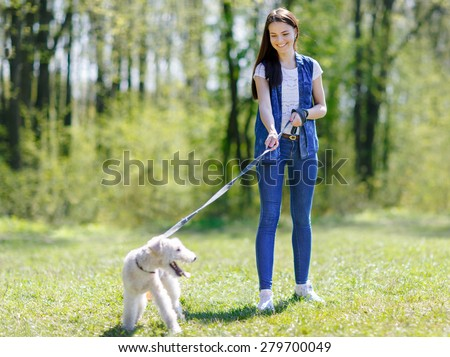 Girl walking with a dog on a leash in a summer park - stock photo