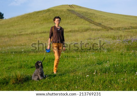 Girl walking with a dog on the background of beautiful scenery - stock photo