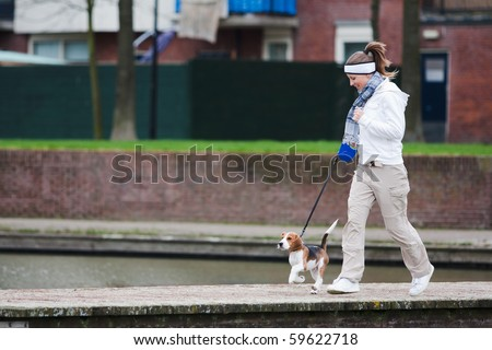 Girl walking with her dog on the leash. Beagle puppy - stock photo