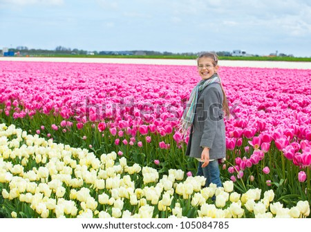 Girl walks between of the colorful tulips field - stock photo
