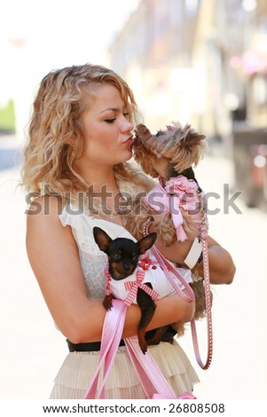 Girl walks with her friends - cute small dogs - stock photo