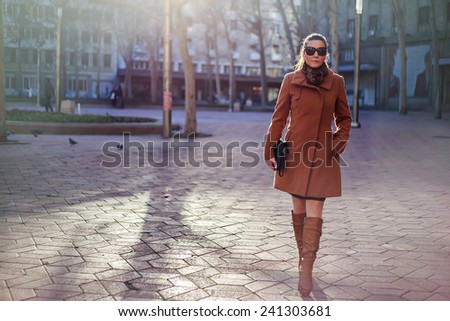 Girl walling and smiling in the city - stock photo