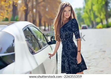 girl want open door of car outside - stock photo