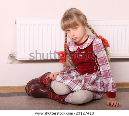 Girl  warm  near radiator.  Energy crisis. - stock photo
