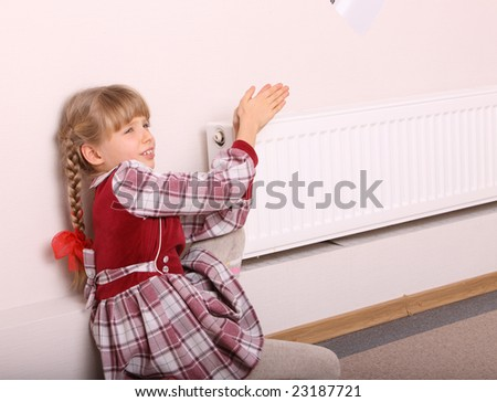 Girl warm one's hands near radiator.  Cold crisis. - stock photo