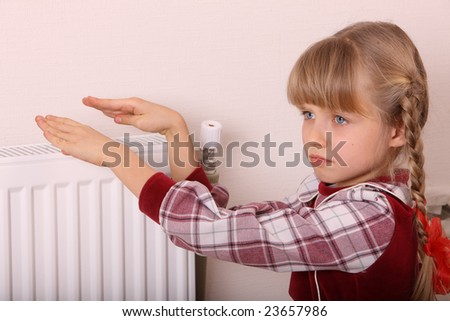Girl warm one's hands near radiator.  Cold crisis.