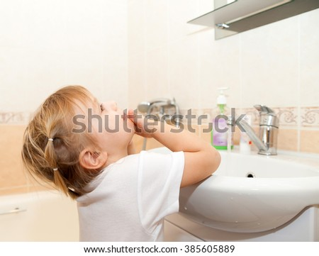 Girl washing  face with soap.