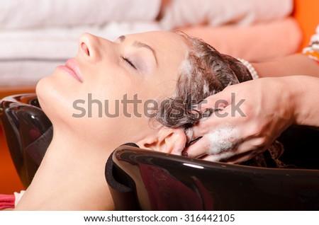 Girl washing hair in hairdressing salon. - stock photo