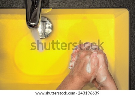 Girl washing her hands in a yellow washbasin - stock photo
