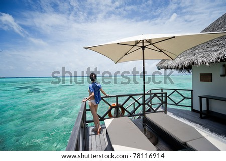 girl watch towards the sea on the deck of water house - stock photo