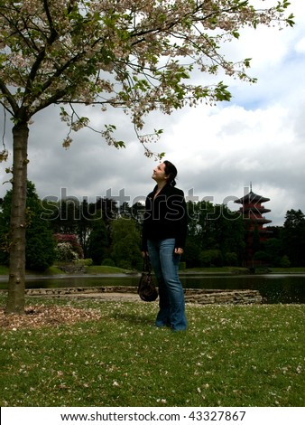 Girl watching at blossom tree against the background of chinese tower, Royal greenhouses, Brussels, Belgium