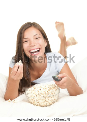 Girl watching movie / TV laughing having fun eating popcorn in bed. Young mixed Asian / Caucasian woman model on lying down in bed.
