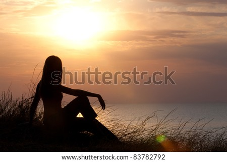 Girl watching sunrise on the grassy cliff - stock photo