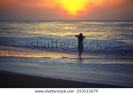 Girl watching the sunrise over the ocean with his hands behind her head - stock photo