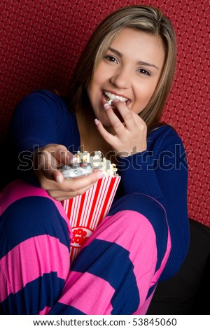 Girl watching tv eating popcorn