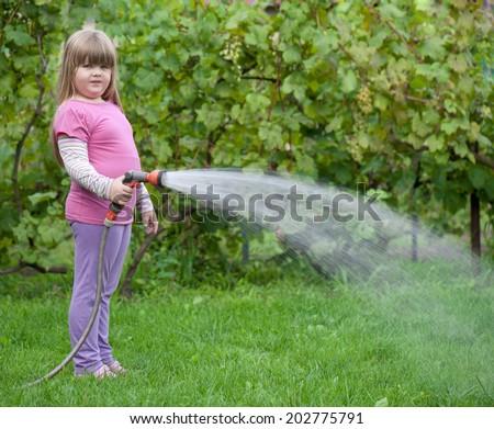 girl watering the grass/girl watering the grass - stock photo