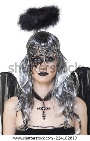Girl wearing a black halloween costume, mask and cross on white - stock photo