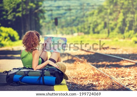 Girl wearing backpack holding map, waiting for a train. - stock photo