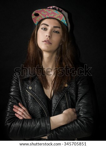 Girl wearing basket cap and leather jacket with crossed arms