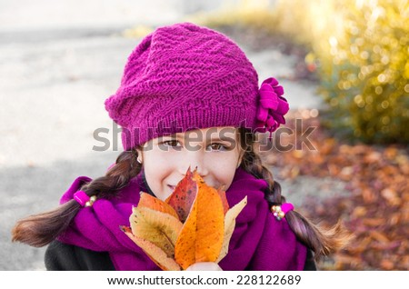 Girl wearing beret and scarf holding autumn leaves - stock photo
