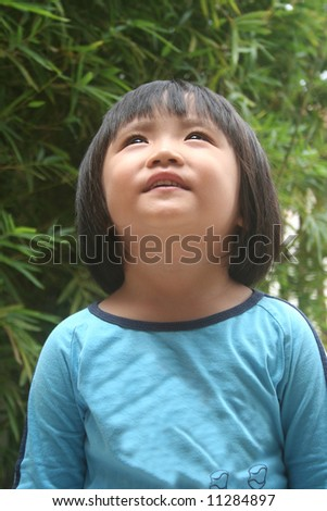 Girl wearing blue tee smiling and looking up - stock photo