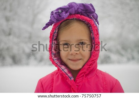 Girl wearing bright red coat in snow - stock photo