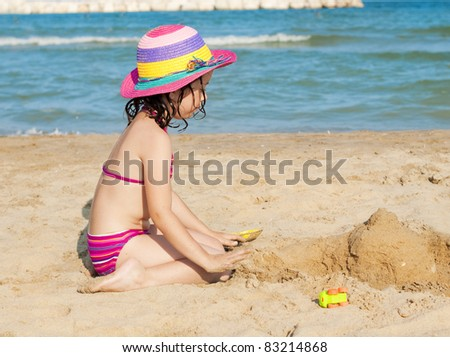 Girl wearing colorful hat playing on the beach - stock photo
