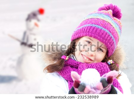 Girl wearing hat, scarf and mittens doing a snowman - stock photo