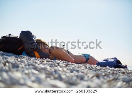 girl wearing in bikini sleeping on the beach  - stock photo
