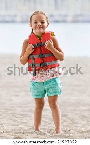 Girl wearing life jacket at beach - stock photo