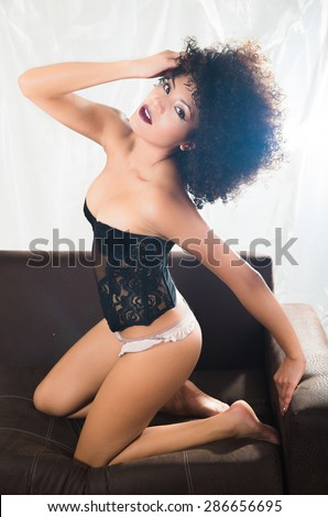 girl wearing lingerie doing sexy pose sitting on her knees in sofa and right hand in hair