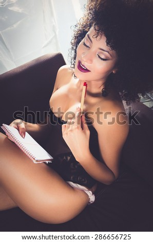 girl wearing lingerie sitting in sofa holding pen and paper looking slightly content