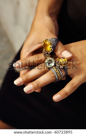 Girl wearing many antique handcrafted Turkish rings with grunge patterns and precious stones - stock photo