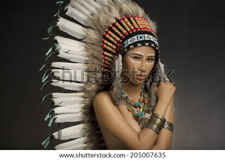 Girl wearing Native American Indian headdress and jewelry and face paint  - stock photo
