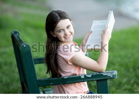 Girl wearing orange shirt outdoors on a park bench reading - stock photo