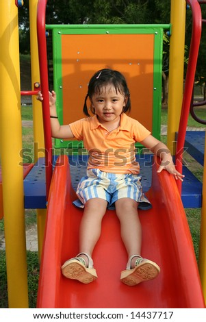Girl wearing orange tee sitting on the slides in the park - stock photo