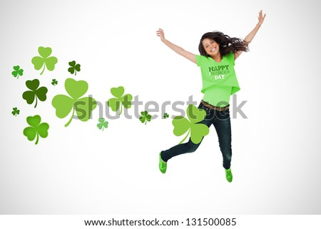 Girl wearing patricks day t-shirt jumping for joy on white shamrock background