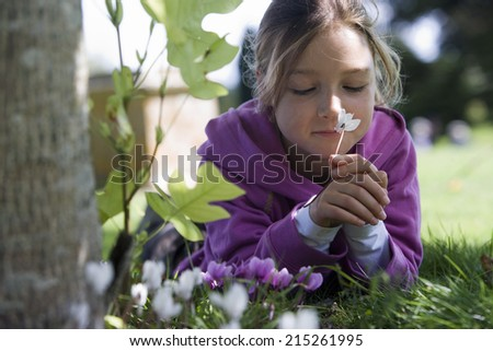 Girl wearing purple hooded top, lying on grass in garden, smelling flower, eyes closed, close-up, surface level (differential focus) - stock photo