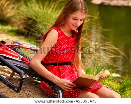 Girl wearing red dress read book on beach of river. Girl arrived on bicycle. Girl leaning near bicycle on river beach in park outdoor. - stock photo