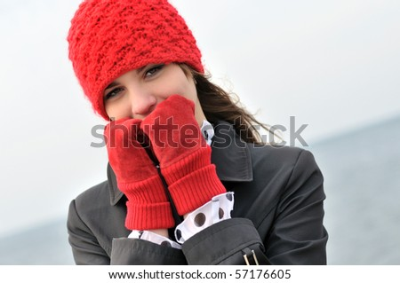 girl wearing  reg hat and red gloves outdoors - stock photo