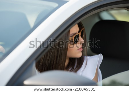 Girl wearing sunglasses driving white car