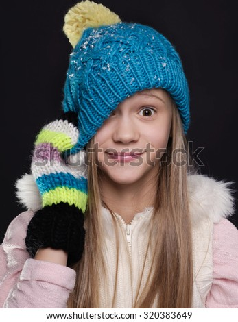Girl wearing winter hat and gloves covered with snow flakes - winter clothes - stock photo