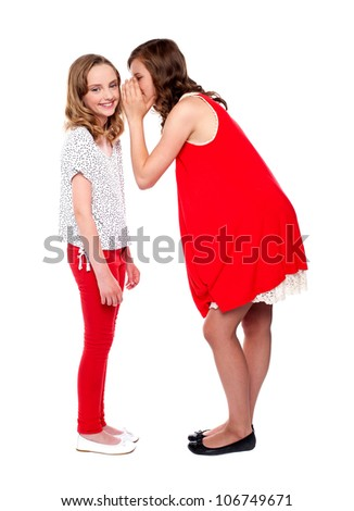 Girl whispering a secret into her friends ear. All on white background
