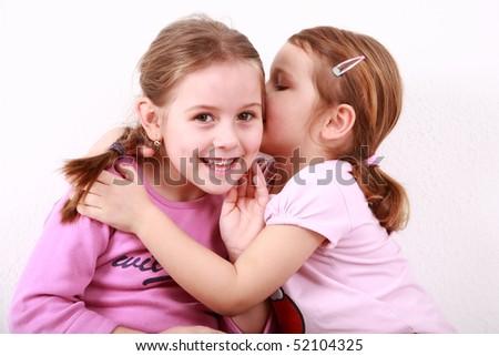 Girl whispering a secret to her girlfriend - stock photo