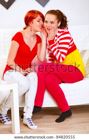 Girl whispering gossips in ear of her interested girlfriend - stock photo