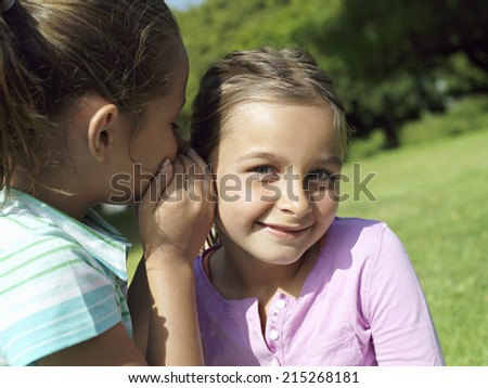 Girl whispering in friend's ear, smiling, close-up