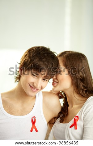 Girl whispering some secrets in her boyfriend�¢??s ear, red ribbons attached to their clothing