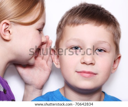 Girl whispers to the boy - stock photo